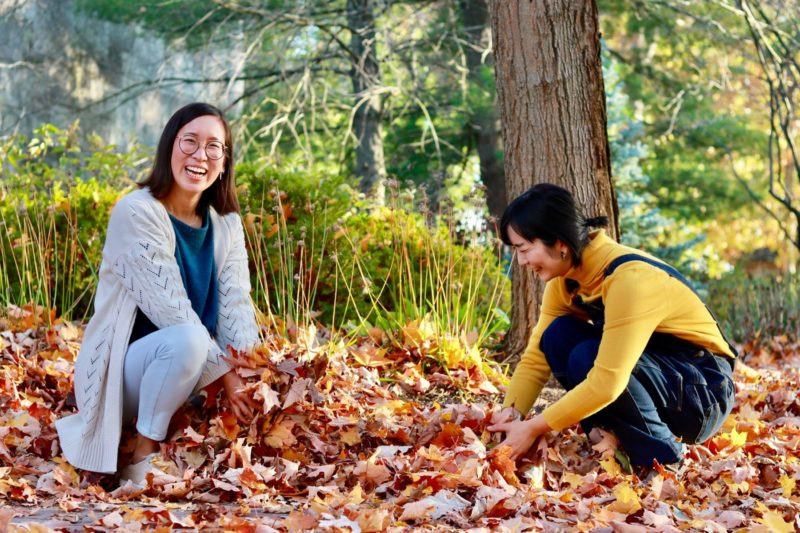 Photograph of Moe Higa and Hanna Kim sitting in fall leaves.