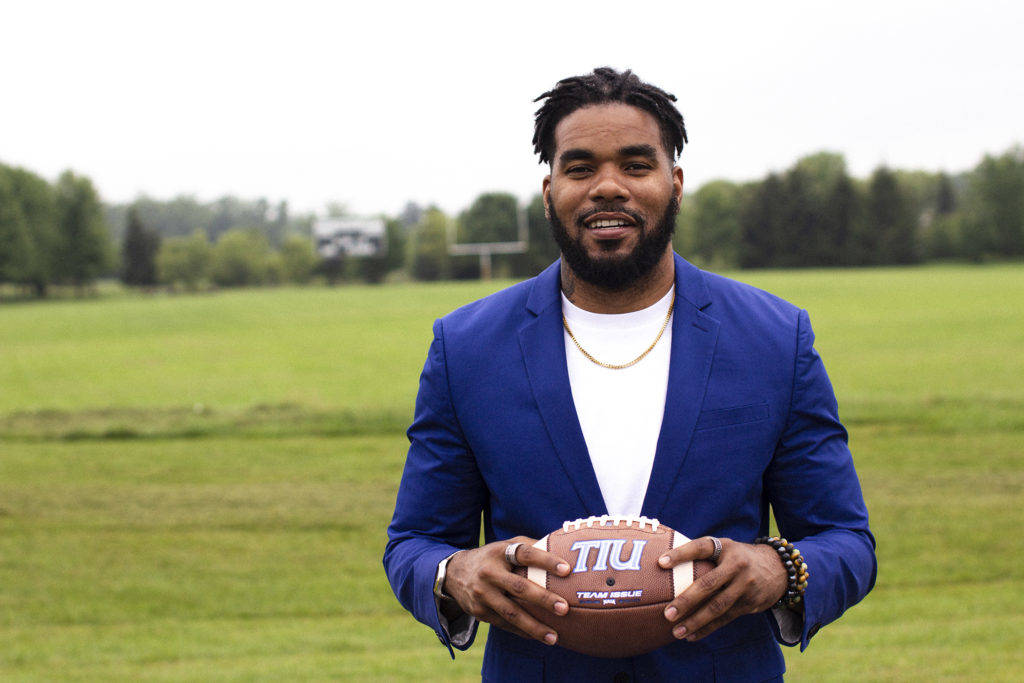 Quintin Demps holding a football in front of the Trojan football field