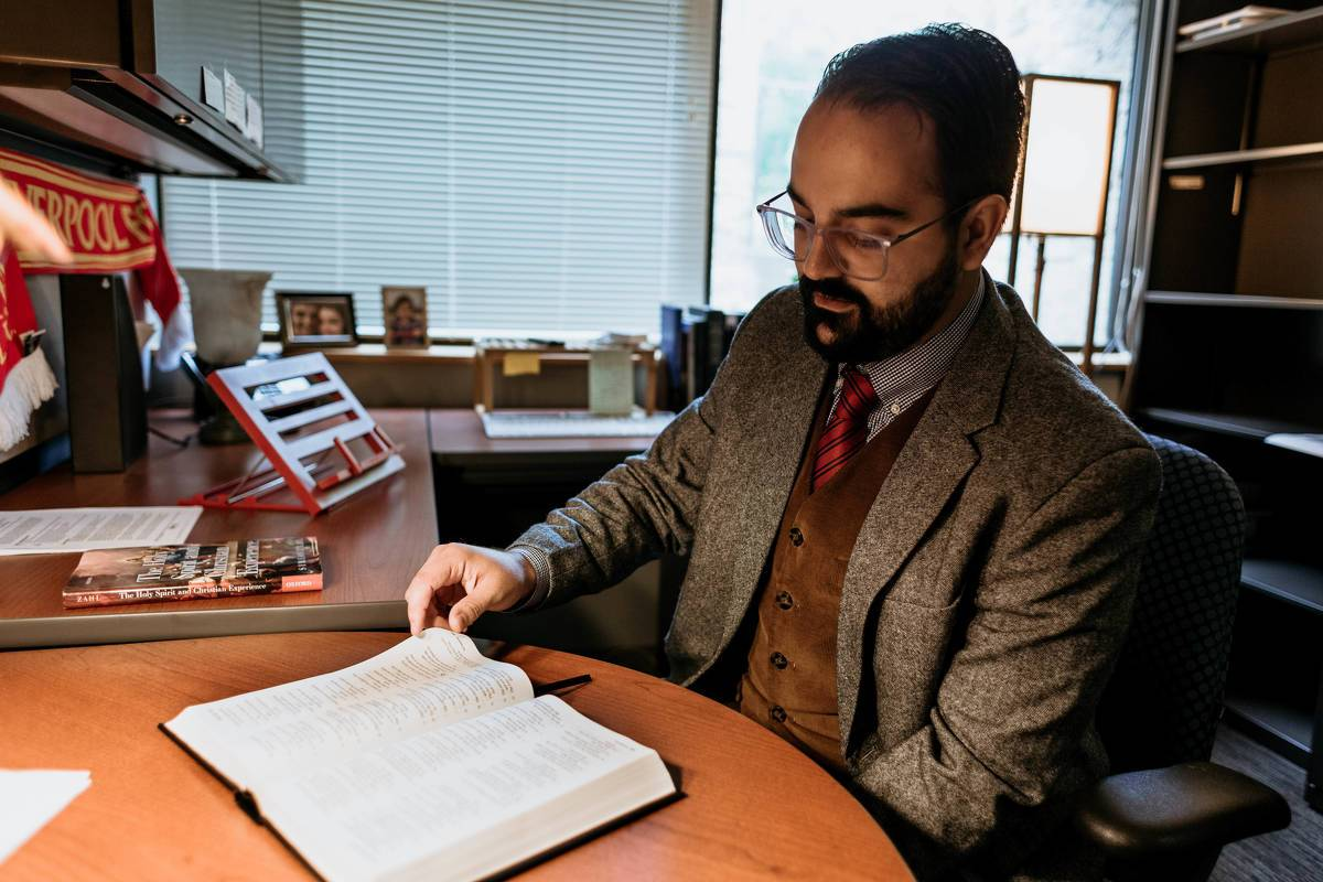 Dr. do Vale reads a Bible in his office